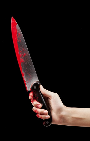 holding a knife: A bloody hand holding a large blood covered knife on a black isolated background