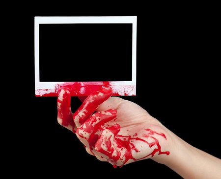 bloodstains: A blood covered hand holding up a piece of blank instant film isolated on black.