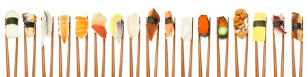 17 different types of sushi being held up in a row with wooden chopsticks isolated on white. Stock Photo