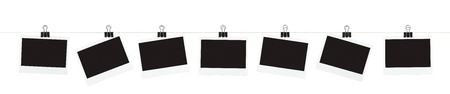 Seven blank pieces of instant film hanging from binder clips on a string isolated on white.