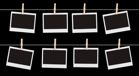 Two rows of four blank pieces of instant film held on strings with  clothespins isolated on black. photo