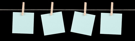 Four blank blue sticky notes held on a string by pegs isolated on a black background. Stock Photo - 13483563