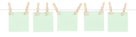 A set of five blank green sticky notes held on a string with clothespins isolated on white. Stock Photo