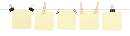 Five blank yellow sticky notes held on a string by various clips isolated on white. Stock Photo
