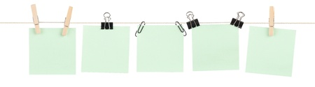 Five blank green sticky notes held on a string by various clips isolated on white.