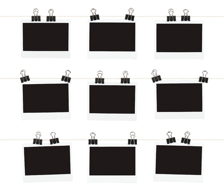 Three rows of three blank pieces of instant film hanging from binder clips on strings isolated on white  Stock Photo