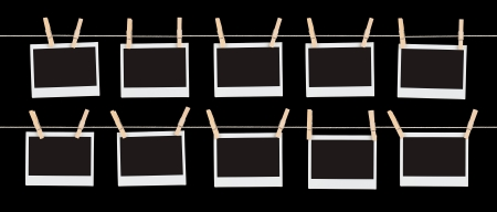 old photo album: Two rows of five blank pieces of instant film held on strings with  clothespins isolated on black