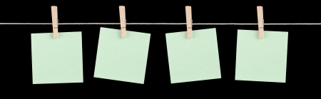 Four blank green sticky notes held on a string by pegs isolated on a black background  photo