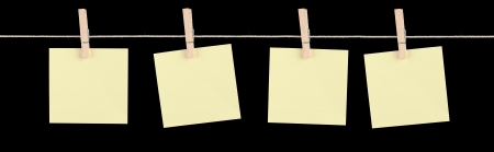 sticky notepaper: Four blank yellow sticky notes held on a string by pegs isolated on a black background  Stock Photo