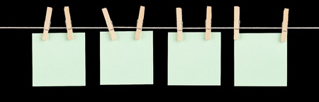 Four blank green sticky notes held on a string with clothespins isolated on black. Stock Photo - 13607746