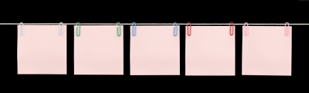 Five blank pink sticky notes held on a string with colorful paperclips isolated on black. Stock Photo - 13607756