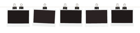 Five pieces of blank film held on a string with binder clips isolated on white.