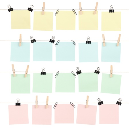 Four rows of colored blank sticky notes held on strings by various clips isolated on white. photo