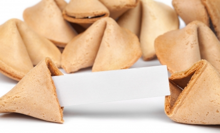 A fortune cookie with fortune paper in front of a pile of other cookies isolated on white.