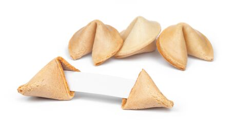 Broken fortune cookie with fortune paper in front of a few other cookies isolated on white. photo