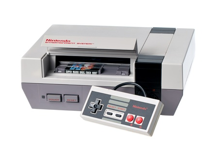 Taipei, Taiwan - July 4, 2012: This is a studio shot of a Nintendo Entertainment System including a controller and game cartridge, made by Nintendo Co. isolated on a white background.