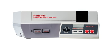 Taipei, Taiwan - July 4, 2012: This is a studio shot of a Nintendo Entertainment System and controller made by Nintendo Co. isolated on a white background. Editorial