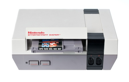 nintendo: Taipei, Taiwan - July 4, 2012: This is a studio shot of a Nintendo Entertainment System including a Super Mario Bros. and Duck Hunt cartridge, made by Nintendo Co. isolated on a white background.