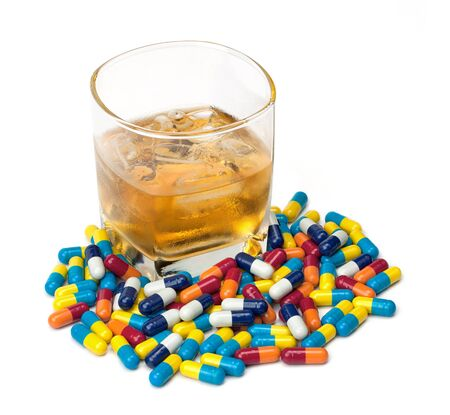surrounded: A glass of whiskey surrounded by pills isolated on white.