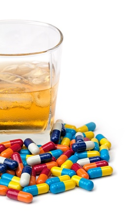 A glass of whiskey with a pile of pills in front of it isolated on white. Stock Photo