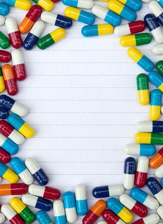 medicamentos: Blanco forrado de papel con las c�psulas de colores haciendo frontera enmarcada. Foto de archivo