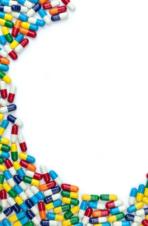 A circular border of colorful pills with copyspace isolated on white.