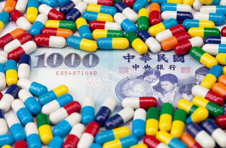 nt: A one thousand NT dollar bill covered with colorful pills with focus on the number 1000.