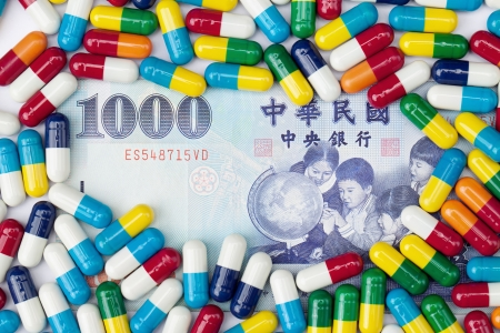 nt: An overhead shot of a one thousand NT dollar bill covered with colorful pills on a white background.