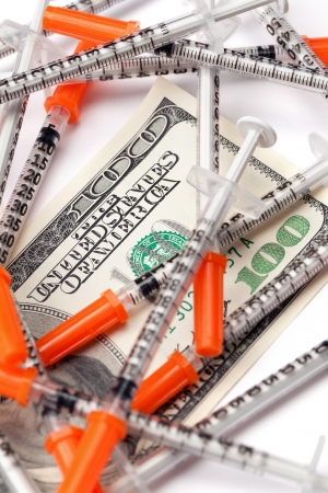 medical bill: A one hundred US dollar  bill covered by medical syringes isolated on white. Stock Photo