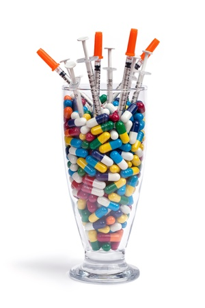 A beverage glass filled with pills and syringes isolated on white. Stock Photo - 16156279