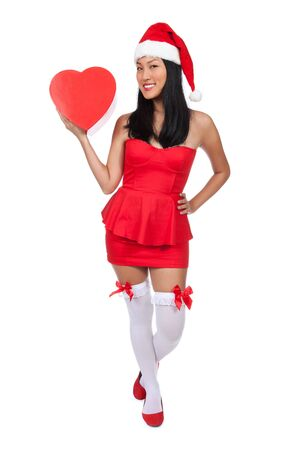 An Asian girl dressed in red and white wearing a Christmas hat holding a heart shaped box. photo