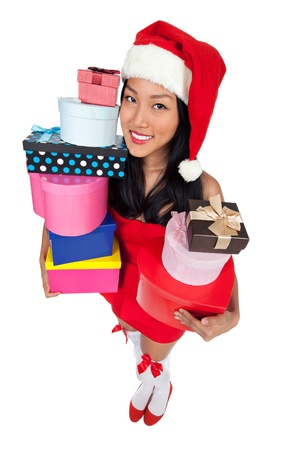 A wide angle shot an Asian girl in a red dress wearing an Xmas hat while holding gifts. photo