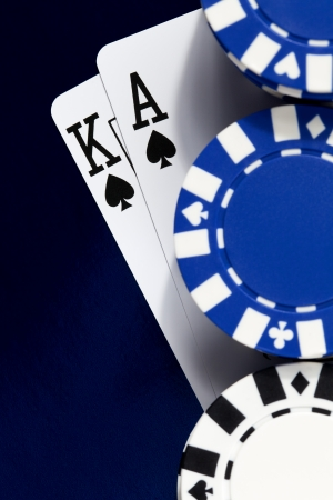 A king and ace of spades under a pile of poker chips on a shiny blue background.