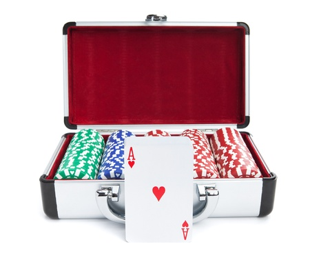 A deck of cards in front of a case containing stacks of poker chips isolated on white. photo