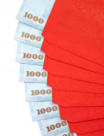 A fan of red envelope with 1000 New Taiwan dollar notes in each of them isolated on a white background. photo