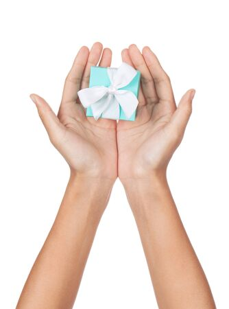 A pair of hands with palms open holding a small blue box with a white ribbon isolated on white. photo