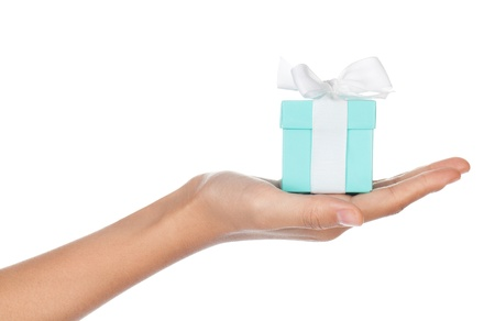 A hand holding a small blue box with a white ribbon in its palm isolated on white. photo