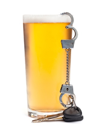 drinking driving: A pint of beer with a miniature pair of handcuffs holding a set of keys