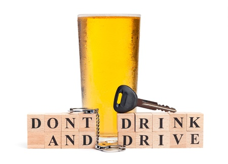A pint of beer with a miniature pair of handcuffs and car key atop blocks spelling out Don