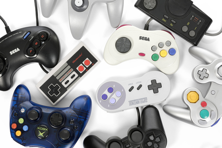 Taipei, Taiwan - February 19, 2018: A collection of retro video game controllers shot from above on a white background. Editorial