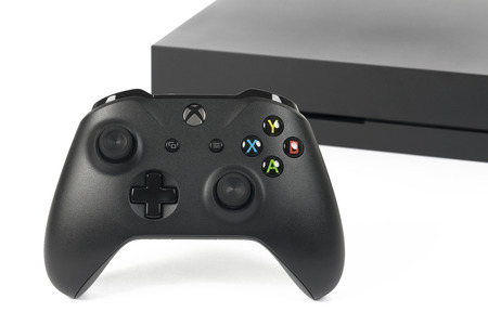 Taipei, Taiwan - February 20, 2018: A close-up studio shot of a Microsoft XBOX One X controller with system in back on a white background. Stock Photo - 100388497