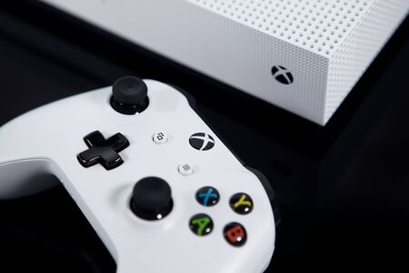 Taipei, Taiwan - June 20, 2019: A white Microsoft XBOX One S system and controller shot on a black surface