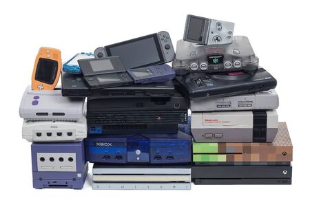Taipei, Taiwan - September 9, 2019: A large pile of video game systems isolated on white.