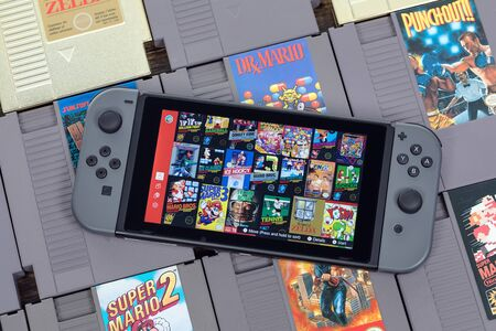Taipei, Taiwan - September 8, 2019: A Nintendo Switch on top some NES cartridges.