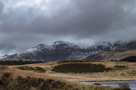 View across Llyn Dywarchen to a snow covered mount Snowdon in the Snowdonia National Park, Wales.