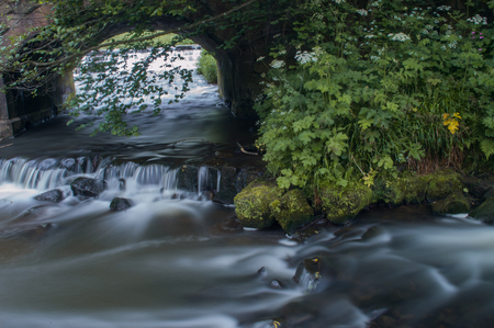 Flowing water turned milky white by a long exposure as it flows around green and brown moss covered rocks.