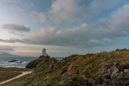 The Llanddwyn island lighthouse, Twr Mawr at Ynys Llanddwyn on Anglesey, North Wales at sunrise. Stock Photo