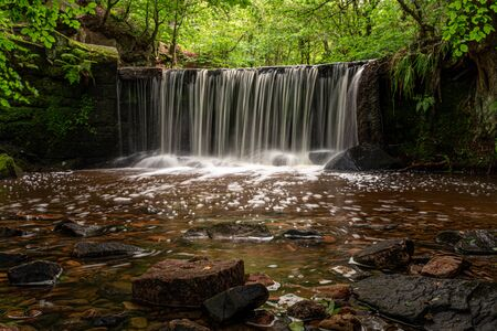 Long exposure of a small waterfall at Kynpersley Reservoir in a secluded glen. Lush vibrant emerald green trees, leaves and ferns, with moss covered rocks.