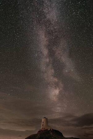 The Milky Way over Llanddwyn island lighthouse, Twr Mawr at Ynys Llanddwyn on Anglesey, North Wales. 스톡 콘텐츠 - 132786673