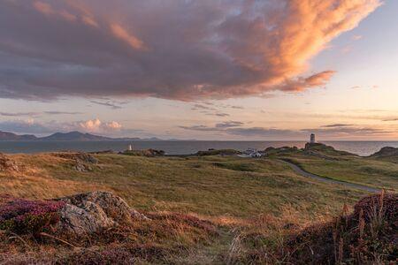 The Llanddwyn island lighthouse, Twr Mawr at Ynys Llanddwyn on Anglesey, North Wales at sunset. 스톡 콘텐츠 - 132786713